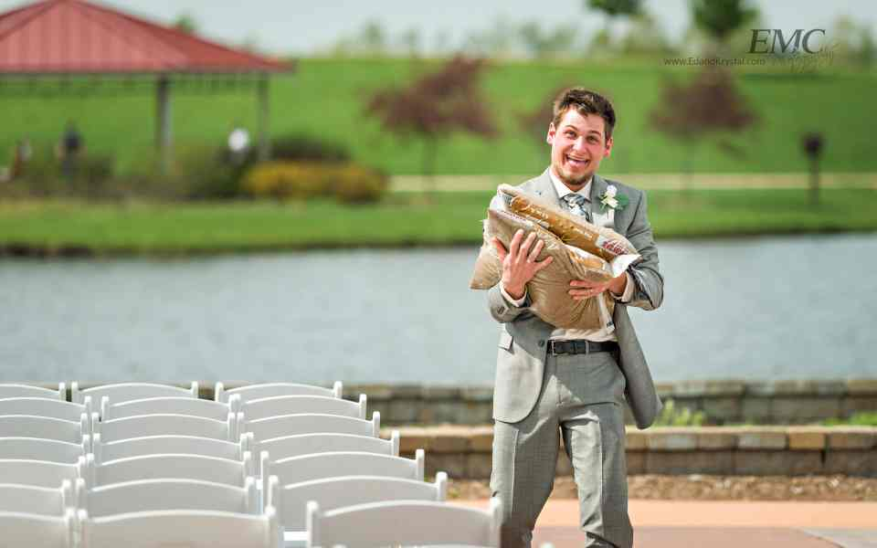 A groomsman grins as he hauls some 50 to 100 lbs of bagged sand away from the altar area after the ceremony.