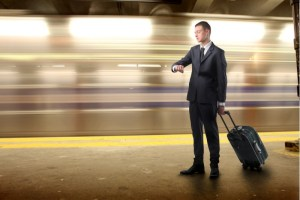 man in subway looking at watch while train speeds by