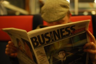 A man reading a business journal.Business news spreads daily through the business journals, newspapers, and magazines.
