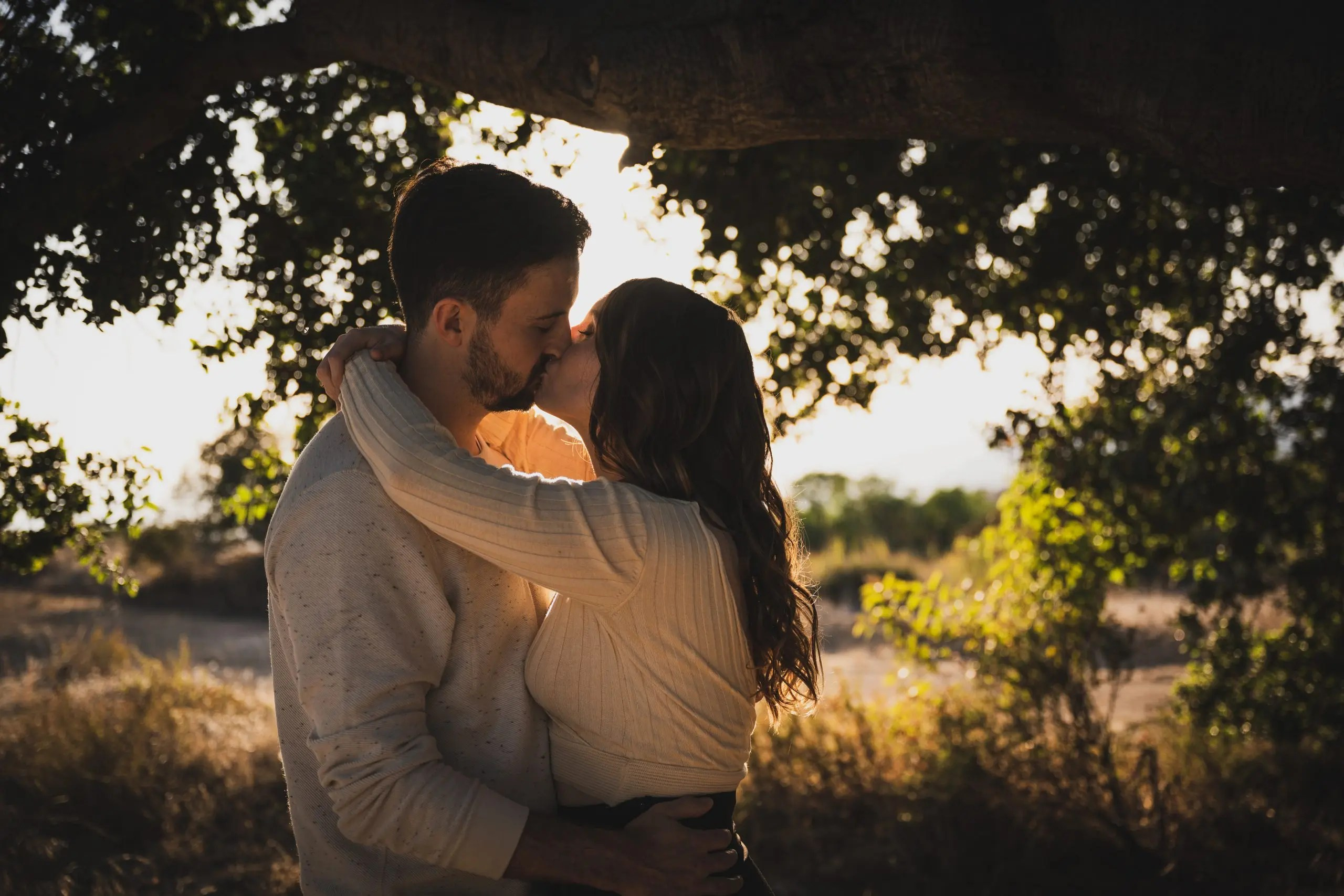 Couple kissing in front of trees outdoors.