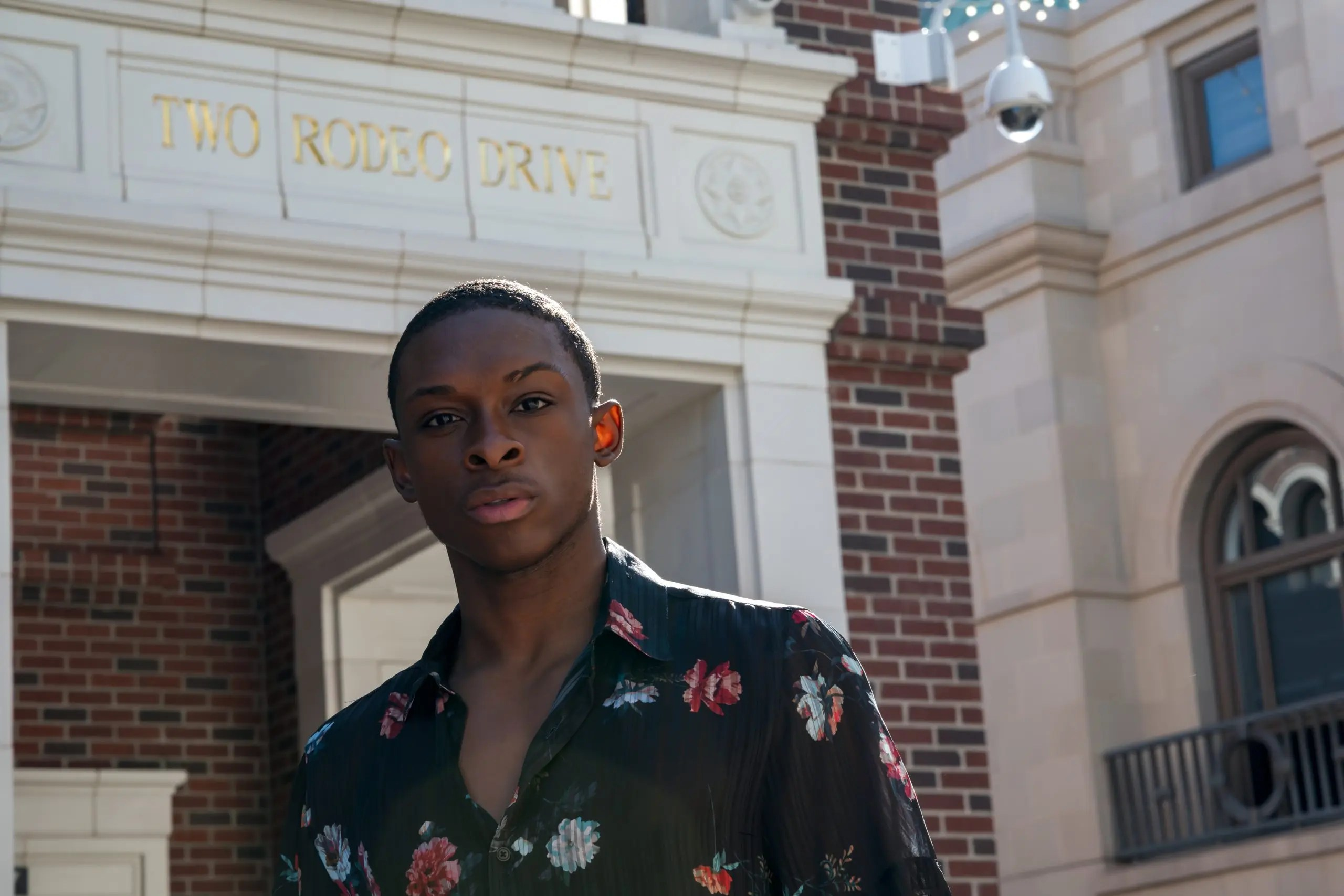 Black male model posing in front of Rodeo Drive in Beverly Hills, California wearing a black floral button-down shirt.