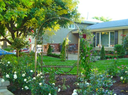 Front yard English garden with gravel patio, roses and fountain