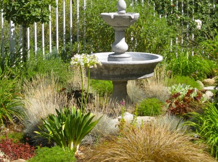 Ornamental grasses surround a two-tiered fountain