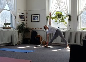Teacher demontrating Utthita Trikonasana (triangle pose), a beneficial pose for beginning yoga students.