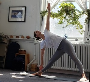 Teacher demonstrating utthita trikonasana (triangle pose), a very beneficial pose for beginners.