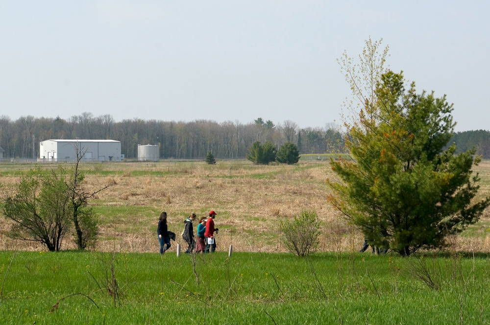 A CHE group touring the reclaimed Flambeau Mine site with the industrial outlot in the background. Photo by William Cronon, 2014. Click to enlarge.