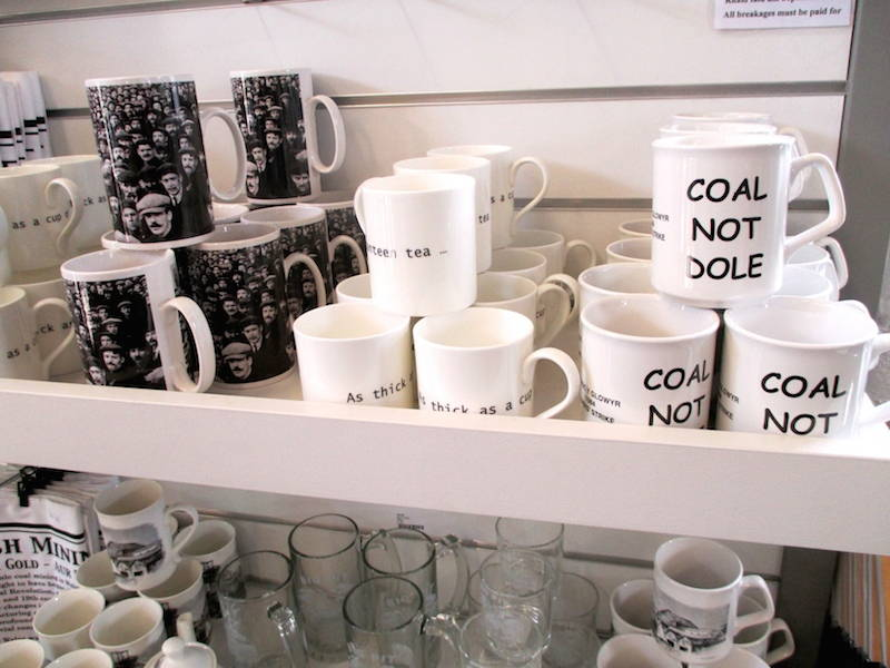 """Mugs from the gift shop at The Big Pit Museum recall the bitter miners strike of 1984-1985. They are emblazoned with """"Coal Not Dole,"""" the slogan of the National Union of Mineworkers. """"Dole"""" is British slang for unemployment benefits. For some, the mugs might simply be nostalgic kitsch but for others in southern Wales, they represent persistent pride in mining as an occupation. Click to enlarge. (Davey, 2014)"""