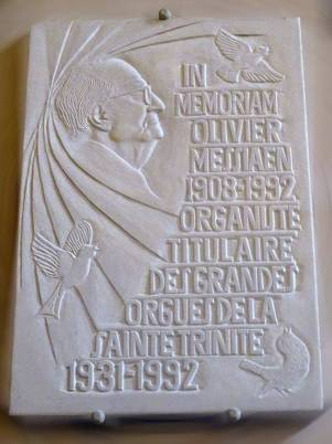 """A white shallow-relief marble plaque, with Messiaen carved in profile, two doves, and a French inscription that reads """"In Memory, Olivier Messiaen, 1908-1992, Organist of the organ of Sainte Trinite, 1931-1992"""""""