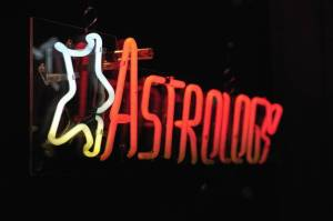"""""""Astrology"""" written in neon with a white neon star, on a black background."""