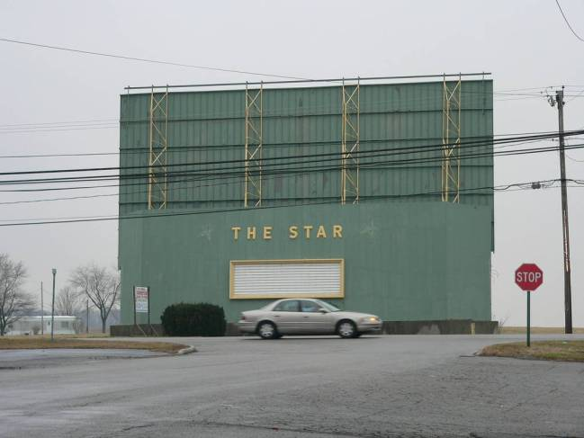 """A blurry car drives past the backside of the abandoned drive-in movie theater, """"The Star."""""""