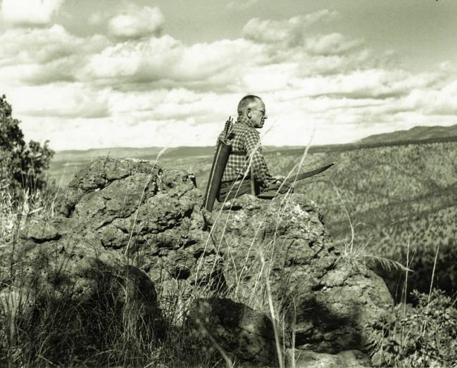 A man holding a bow with a quiver of arrows on his back sits on a rocky outcorop looking down over a expansive vista.