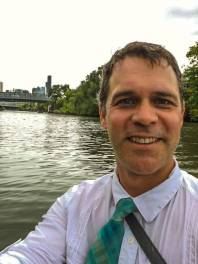 A man in a blue and green necktie poses for a selfie in the middle of a river with an urban skyline in the background.