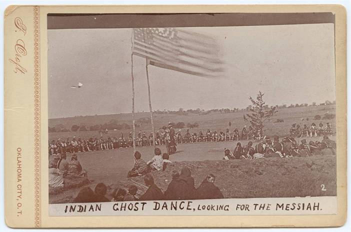 """A circle of Native people watch dancers beneath U.S. flags in a photo labeled """"Indian Ghost Dance, looking for the Messiah."""""""