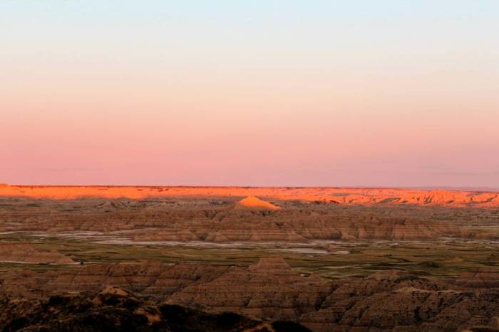 Sun kisses the peak of a badlands formation above a vast expanse of undulating terrain.
