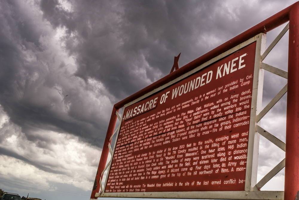 """A large red metal sign, shot from below against a cloudy sky. The title reads """"Massacre of Wounded Knee,"""" with the word """"Massacre"""" carved onto a panel added to the top of the sign."""
