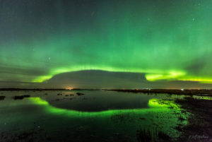The bright green rays of the auroa are reflected in the water.