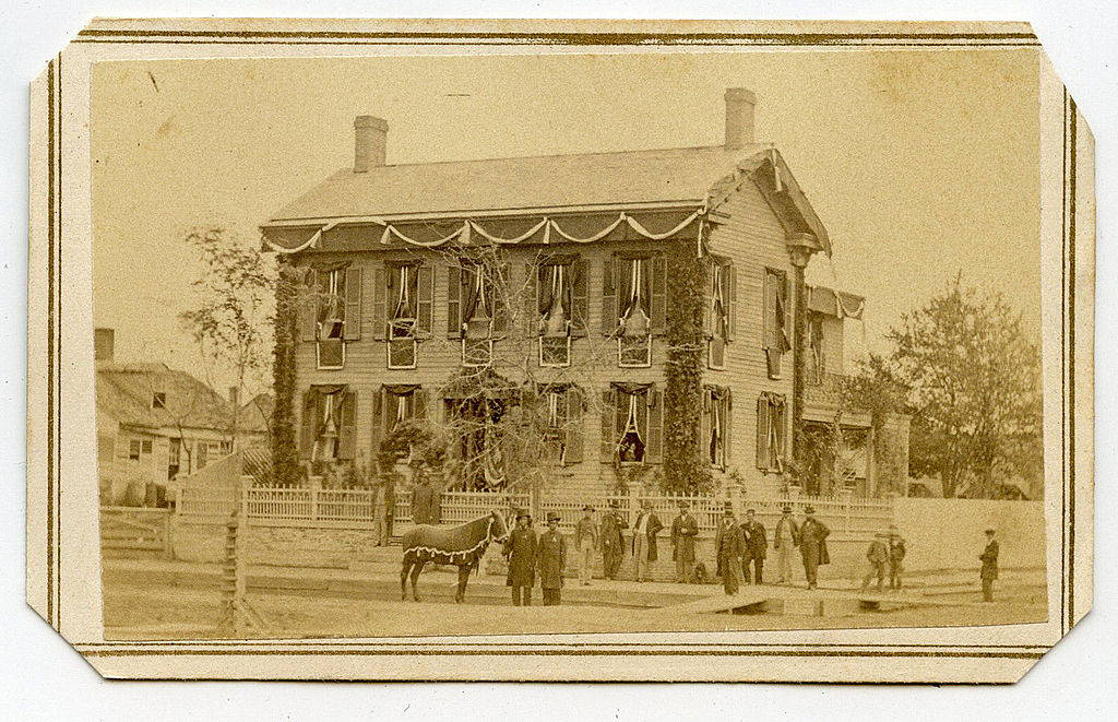 In this black-and white photograph there is two-story corner-house with funeral bunting in the background. In the foreground, bystanders gather on the corner and a horse waits at the curb.