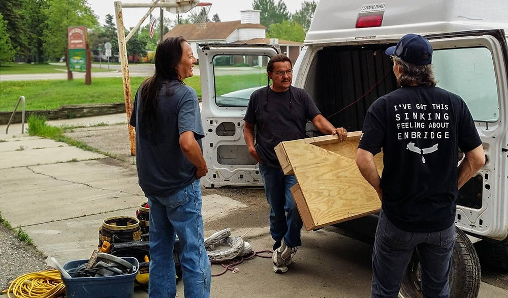 """Three men chat at the back of a white van with tools at their feet. One wears a shirt that reads """"I've got this sinking feeling about Enbridge."""""""