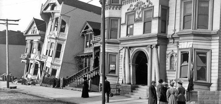 """A group of people stand in front of houses that pitch and lean into one another on the """"Drunken Row"""" of Victorian homes at Howard Street (now Van Ness) between 17th and 18th."""