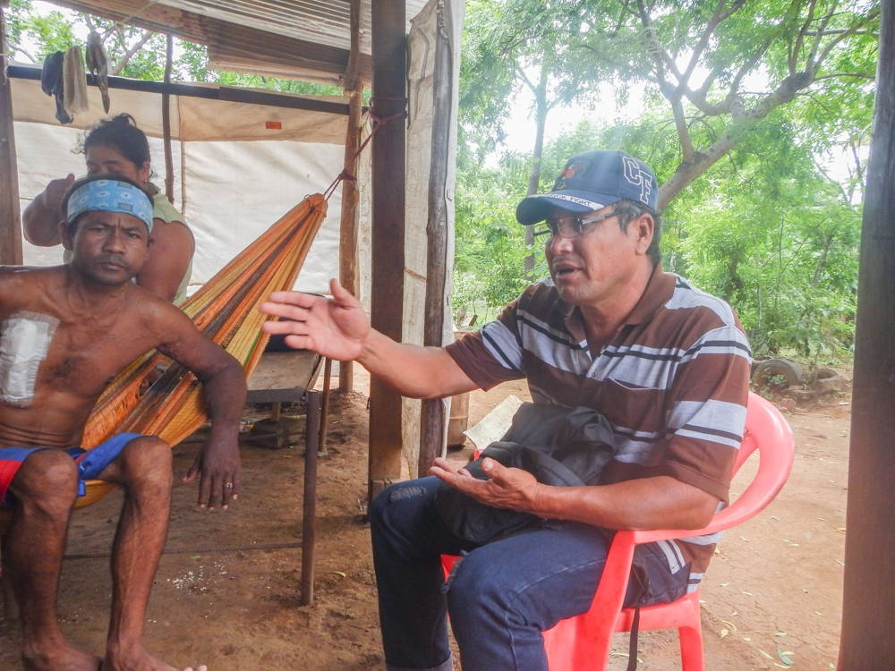 A man with a large bandage on his chest sits in a hammock speaking with his neighbor, seated in a plastic chair.