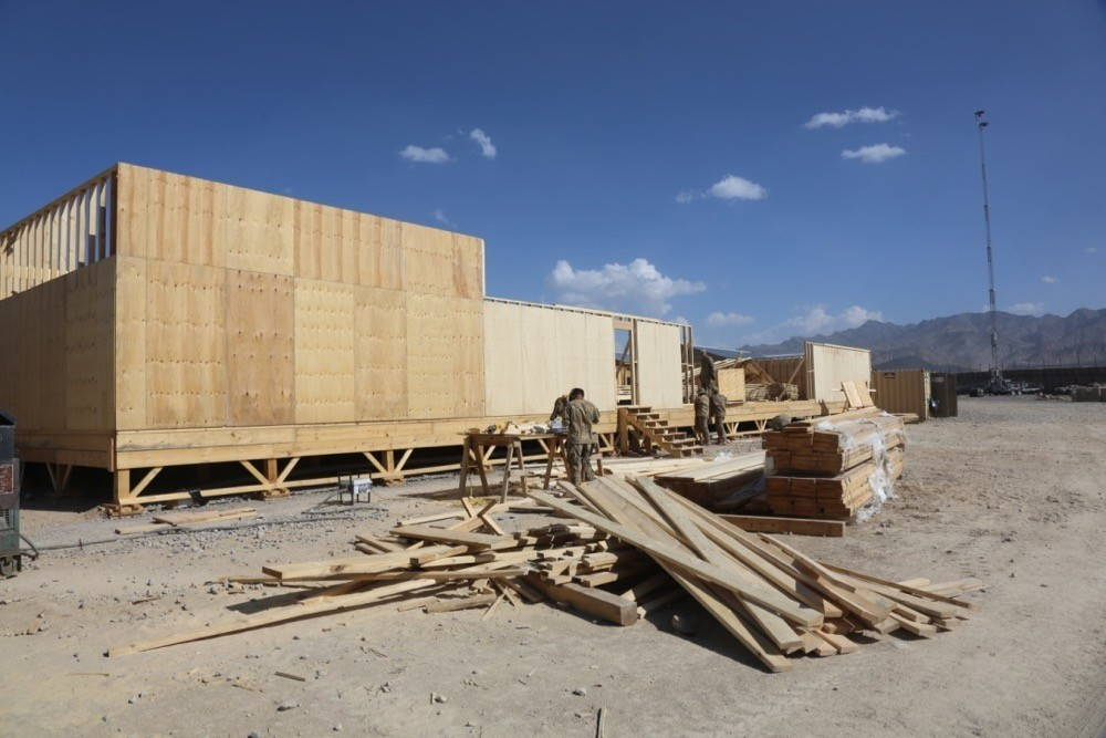 a plywood building mid-construction with a pile of plywood next to it