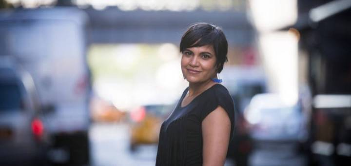 Jaskiran Dhillon stands in the foreground of a blurry city scene with yellow taxicabs behind her