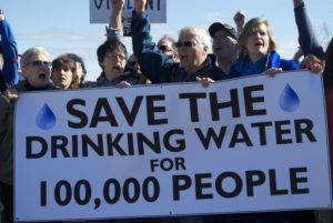 """Sandra Steingraber and three other protesters, surrounded by others, shout and hold a sign that reads """"Save the Drinking Water for 100,000 People"""""""