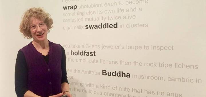 """Lynn Keller stands in front of several lines of poetry written in grey words on a wall. The words """"en-wrap"""" """"swaddled"""" """"holdfast"""" and """"Buddha"""" are emboldened."""