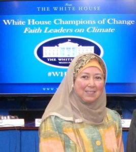 """Huda Alkaff, in a taupe hijab, smiles at the camera in front of a blue screen that reads """"White House Champions of Change / Faith Leaders on Climate"""""""