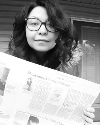 """A brunette woman with round glasses hols up a New York Times review of her recent book. The article title reads, """"Shattering a Pattern of Silence"""""""
