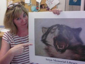 Stephanie Rutherford holds a large poster of a howling wolf and points to it