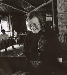 Val Plumwood looks through reading glasses down at her laptop and smiles in a room with a woman sitting in the background in this black and white portrait