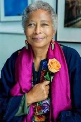 The writer Alice Walker poses for a photograph wearing a bright purple scarf and clutching a bright peach rose.
