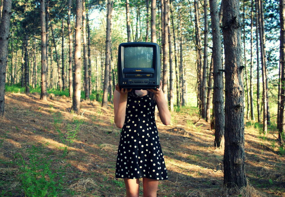 A young woman in a black and white polka dot dress stands in the woods. She holds a small television in front of her face. The featured image for a post on environmental themes in pop culture.