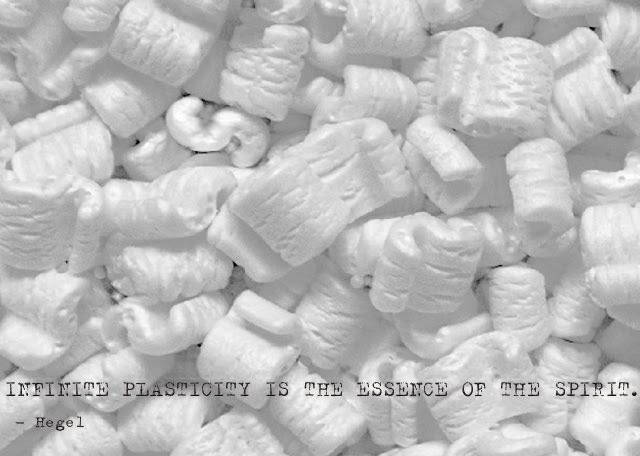 """A photograph of white Styrofoam packing peanuts with a quotation from philosopher G.W.F Hegel in typewriter font bannered across the peanuts that reads """"infinite plasticity is the essence of the spirit"""""""