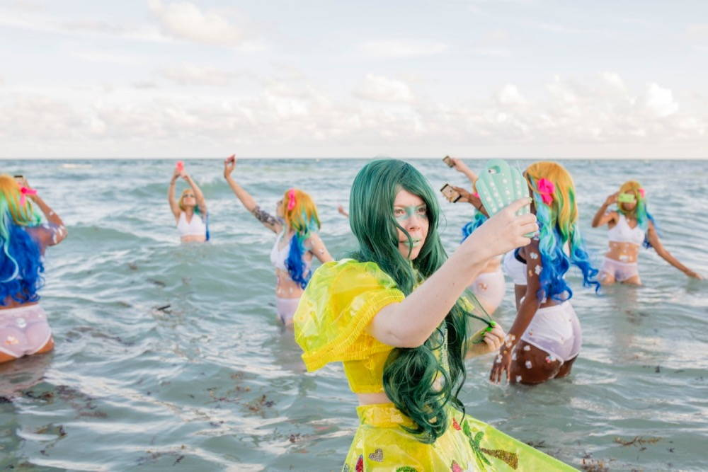 Kate Durbin, artist, takes a selfie while standing in thigh-height waves and wearing a yellow plastic dress with Hello Kitty icons and a long, green wavy wig. In the background, other women wearing white underwear and rainbow-hued long wigs also take selfies while standing in the waves.