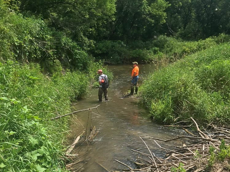 Two scientists standing in a small creek.