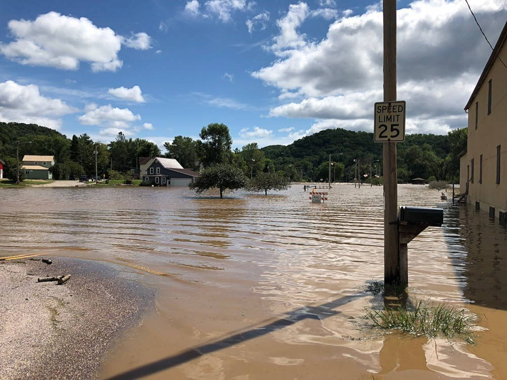 A historic downtown area is flooded by murky brown water as the Kickapoo River submerges the town.