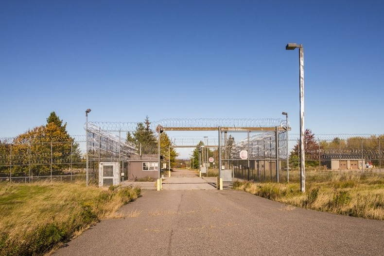 A metal gate over the driveway into a fenced-in prison yard.