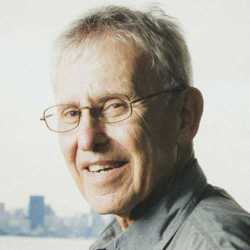 A man with glasses and grey hair turns his head toward the camera and smiles with the New York skyline in the far distance.