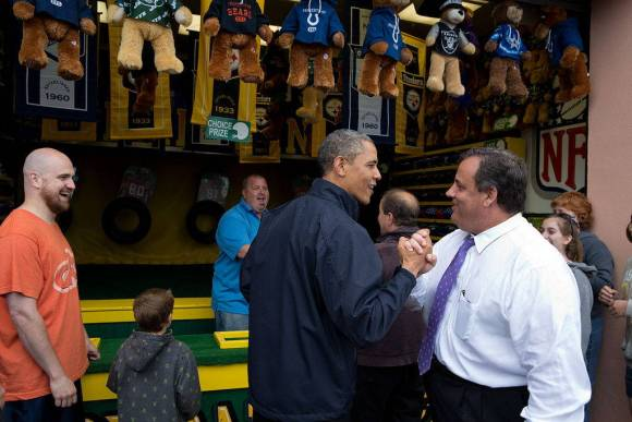 Obama (left) and Christie clasp hands and smile at each other in front of a carnival game with teddy bear prizes hanging above them.