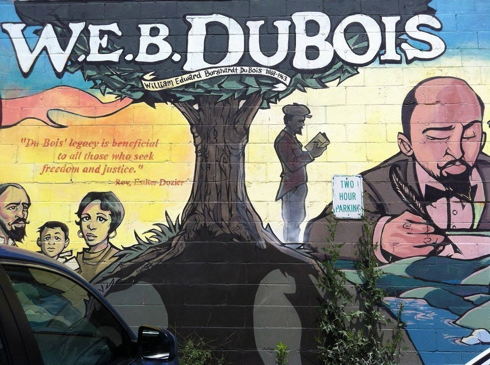 """A mural on a brick wall reads """"W. E. B. Du Bois / William Edward Burghardt Du Bois 1868-1963 / """"Du Bois' legacy is beneficial to all those who seek freedom and justice"""" - Rev. Esther Dozier"""" The images are of Du Bois reading, writing, and with his wife and child. A car is parked in front of the mural and a two-hour parking sign sits in the middle of it."""