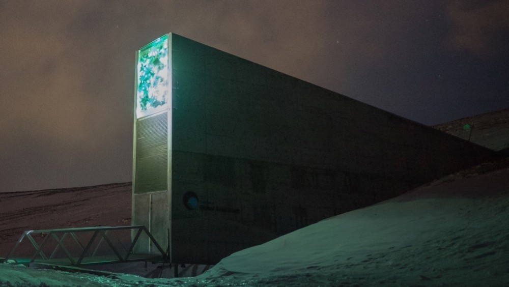 An imposing, futuristic, and slim concrete building juts out of the side of an icy covered slope. Pictured at night, a portion of the top part of the front of the building is illuminated with blue and green lighting. A small and short bridge leads into the building.