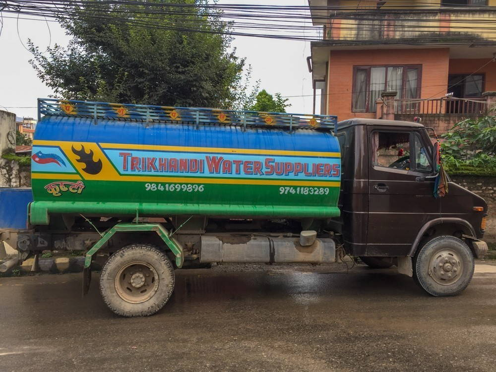 A large, multi-colored water truck parks on the street in front of a home.