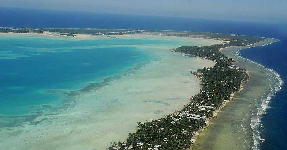 A narrow island sits between a blue bay and a dark blue ocean.