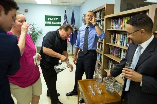 Five people, including President Obama wearing a blue shirt and tie, stand around a small table while another man pours water for them to drink.