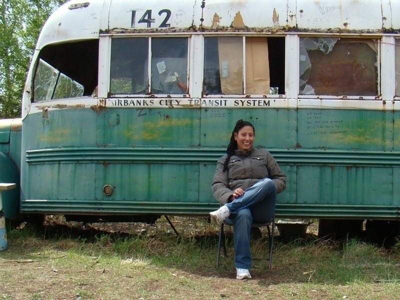 A person sits on a folding chair in front of a green, rusted bus