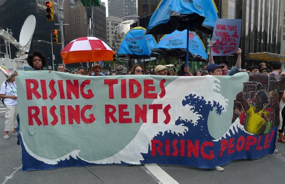 A crowd of people participating in a climate march holding a sign that reads rising tides, rising rents, rising people