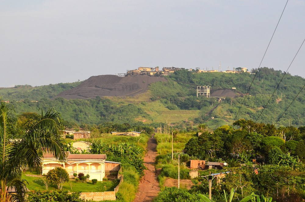 A dirt road leads through the middle of a lush forest. Flanked by houses, the road leads to the top of a mountain, which is mostly exposed rock due to mining.