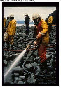 a person equipped with a respirator works to clean the Exxon Valdez oil spill.